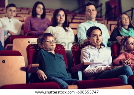 Group of pleasant  smiling  people watching movie attentively in cinema