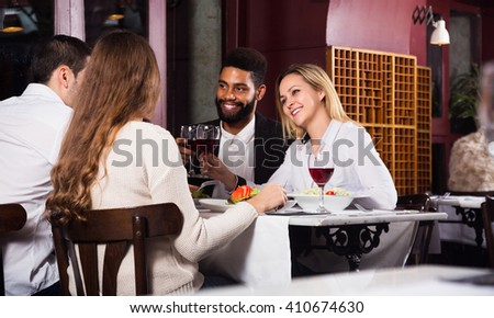 Group of positive adults having dinner in restaurant and laughing