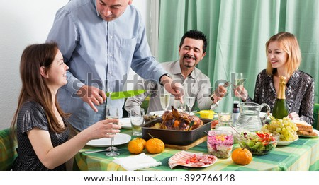 Group of positive friends eating at festive table and chatting