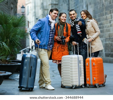 Group of positive friends shooting mutual portrait on cell phone outdoors - stock photo
