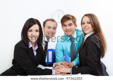 group of positive happy smile young business people pile of hands at desk office, businesspeople putting their hands on top of each other, meeting looking at camera, concept of team, working together