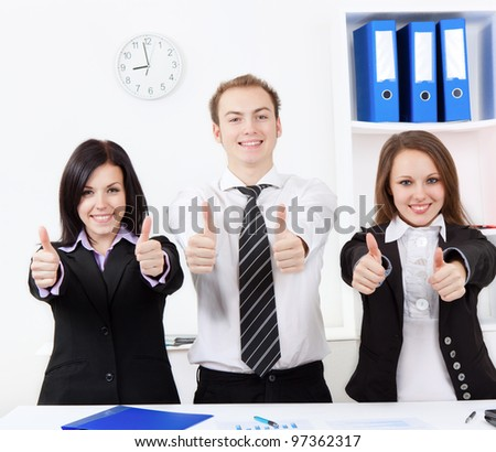 group of positive happy smile young business people show thumb up sign hand gesture at desk office, businesspeople meeting looking at camera, concept of team, working together