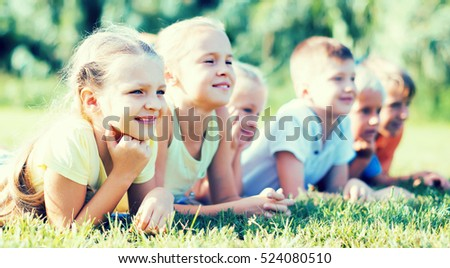 Group of positive kids in elementary school age lying on green grass in park
