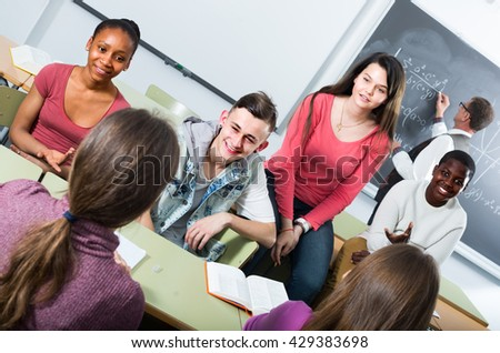 group of positive school pupils taking a rest together indoors - stock photo
