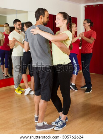 Group of positive spanish people dancing salsa in studio - stock photo