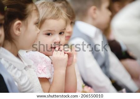Group of preschool children sits on morning performance in kindergarten. - stock photo