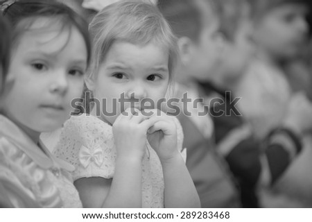 Group of preschool children sits on morning performance in kindergarten. - stock photo