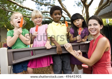 Group of preschool 5 year old girls eating popsicles in daycare with teacher - stock photo