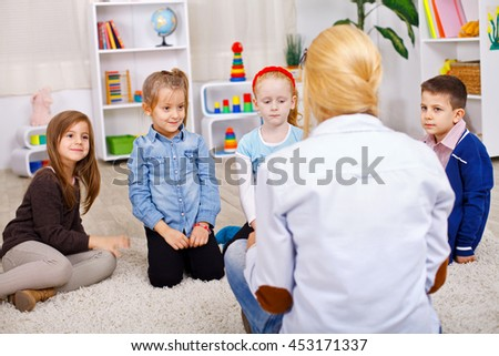 Group of preschoolers listening to a teacher while she's reading them a story