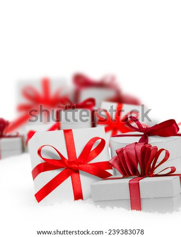 Group of presents with red ribbons on white background, defocused presents behind; white space for text - stock photo