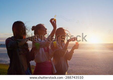 Group of pretty girlfriends blowing bubbles at sunset in bikinis enjoying sunset on summer vacation