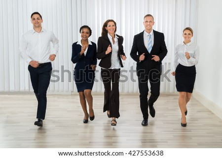 Group Of Professional Businesspeople Together Running In Office - stock photo