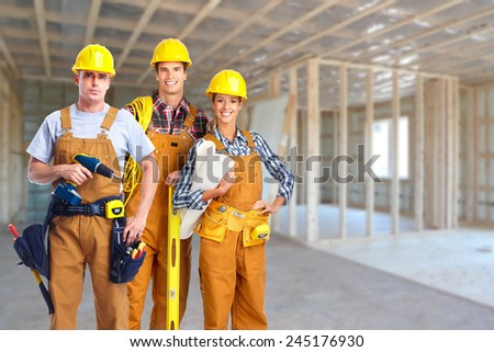Group of professional construction workers in  new house. Renovation. - stock photo