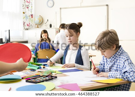 Group of pupils drawing at a common desk during art classes