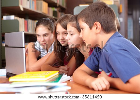 Group of pupils looking at the laptop in school library