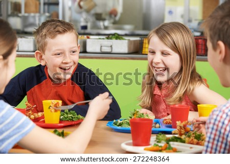 Group Of Pupils Sitting At Table In School Cafeteria Eating Meal - stock photo
