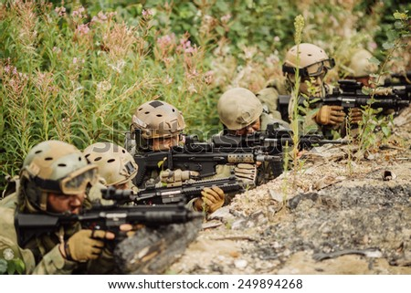 group of rangers hiding in the trenches and firing - stock photo
