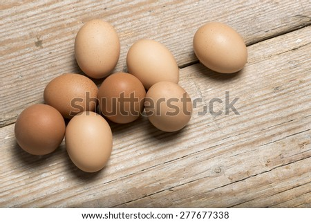 group of raw eggs on wooden table - stock photo