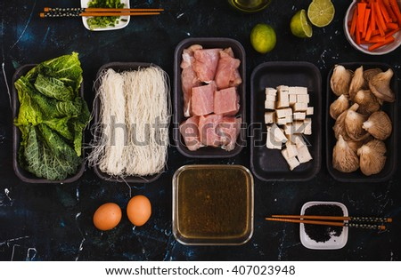 Group of raw ingredients for asian ramen soup. Rice Noodles, chicken breast,  spring onion, tofu cheese, mushrooms, broth bowl, kale leaves in packaging tray with chopstick and black sesame seeds. - stock photo