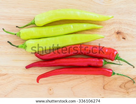 Group of red freshly picked ripe chili peppers on wooden background. Red chilies contain large amounts of vitamin C and small amounts of carotene (provitamin A), top view - stock photo