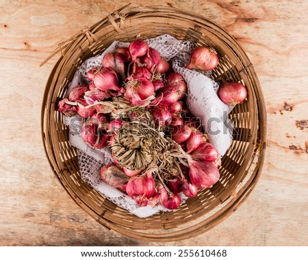 Group of red onions in a wooden basket on the table. - stock photo