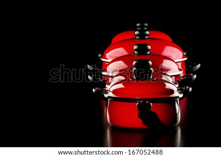 Group of red pans in a black background - stock photo
