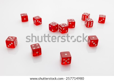 group of red transparent dice laying in mess on white reflective background
