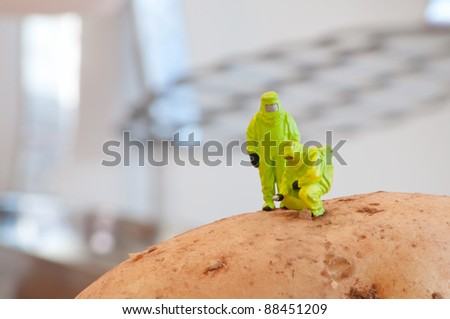 Group of Researchers in protective suit inspecting a potato. Genetically modified food concept - stock photo