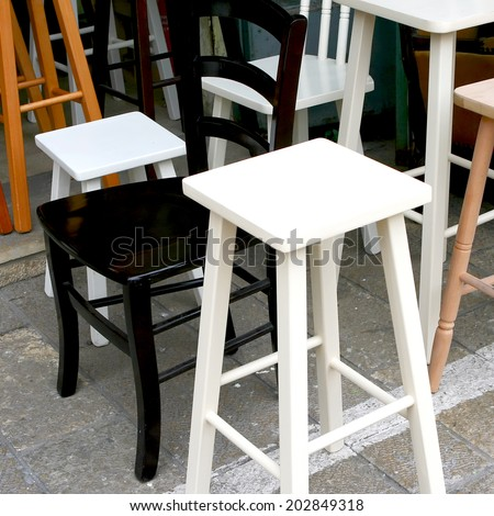 Group of retro wooden chairs for kitchen, dining room and office  on a flea market street . Finishing: staining and varnishing, colors: white, black, brown and natural. Useful for background.