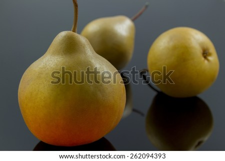 group of ripen pears  on black reflective  background with selective focus