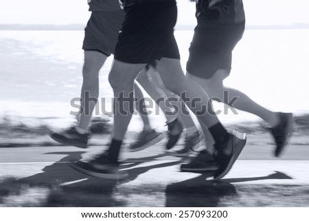 Group of runners compete in the race on coastal road. Blurred motion - stock photo