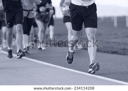Group of runners compete in the race on coastal road. Monochromatic - stock photo