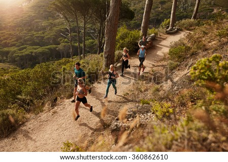 Group of runners in a cross country race. Young people running in nature. Trail running workout. - stock photo