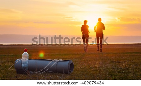 Group of runners training outdoors exercising at sunset in amazing landscape nature. Fit handsome athletic male and female working out for marathon run outside in summer. Couple, man and woman sport.