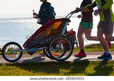 Group of runners with child, compete in the race on coastal road