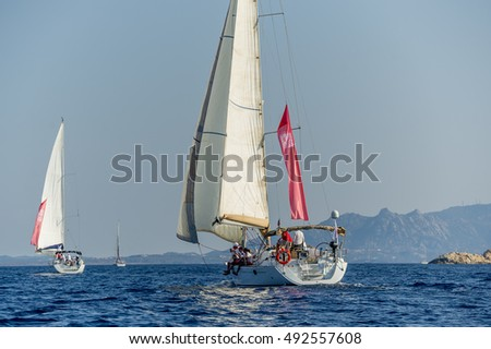 Group of sailboats under the hoisted sails in the Mediterranean. Sardinia, Italy.