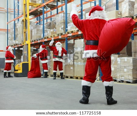Group of santa clauses working together in storehouse - stock photo