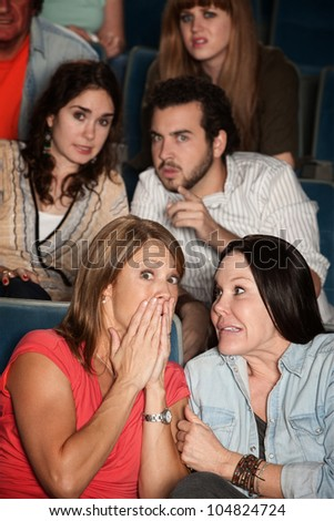 Group of scared men and women in a theater - stock photo