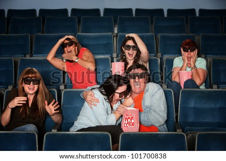 Group of scared people with 3d glasses screaming in a theater - stock photo