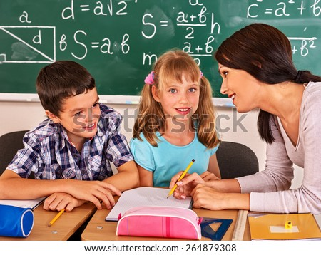 Group of school child with young teacher sitting on desk in classroom. - stock photo