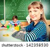 Group of school children studying in classroom. - stock photo