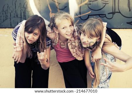 Group of school girls having a fun at the graffiti wall - stock photo