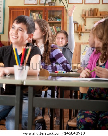 Group of schoolchildren at classroom during a lesson raising hands - stock photo