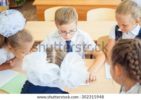 Group of schoolchildren or kids at school classroom sitting at a desk and help each other with their homework. Concept of teamwork among students