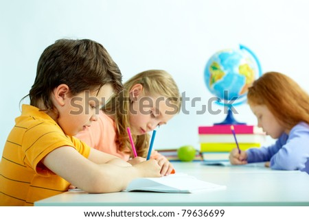 Group of schoolmates drawing at lesson - stock photo