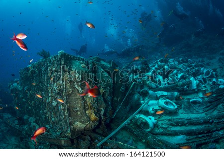 Group of Scuba Divers diving famous, one of the top ten dive sites in the world, where ship Yolanda craned leaving all the material for bathrooms at sea flor that is now home to numerous colorful fish - stock photo