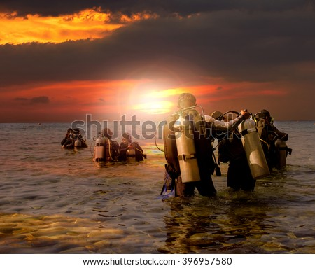 group of scuba diving preparing to night diving at sea side against beautiful sun set sky - stock photo