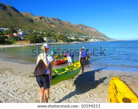 Group of sea kayakers gets ready for trip. Shot in Strand, Western Cape, South Africa. - stock photo