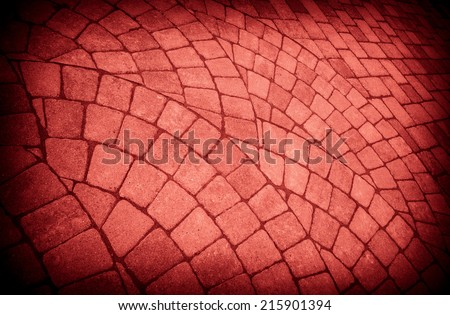 Group of semi circle patterns of pavers for background with red filter applied. - stock photo