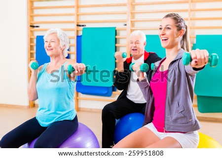 Group of senior and young people at physiotherapy doing exercises - stock photo